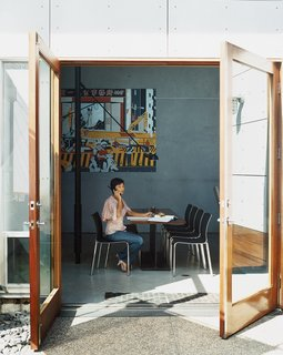 """May Lawrence sits at the dining table, which features mahogany planks attached to an actual I beam. Above her sprawls a Rigo 99 painting of a bustling Taipei street scene, which according to Ward helps import some """"city energy"""" into the suburbs."""