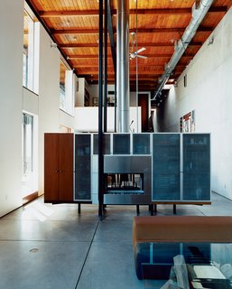 The New Suburbanism - Photo 3 of 10 - David Baker and cabinetmaker Thomas Jameson designed the freestanding fireplace / media console, which effectively divides the more formal living room from the dining and gathering space while concealing cords and other clutter.
