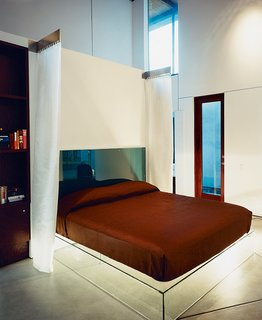 The New Suburbanism - Photo 8 of 10 - The glass platform bed is backed by a headboard of two sheets of lucite embedded with aquamarine wool from Maharam. Hanging pillow-side, electroluminescent draperies glow in the dark.