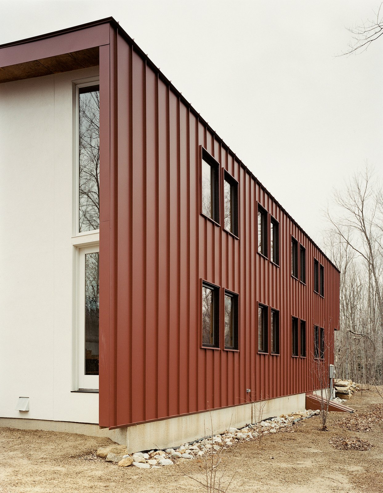"""Exterior, House Building Type, Metal Siding Material, and Flat RoofLine To avoid constant maintenance issues—after all, """"durability is part of sustainability,"""" Gaffney states—the roof is clad in standing seam metal and the siding is composite plastic decking, rather than easily weathered wood.  Photo 9 of 10 in Gaffney House Dining Room from Leave it to Beavers"""
