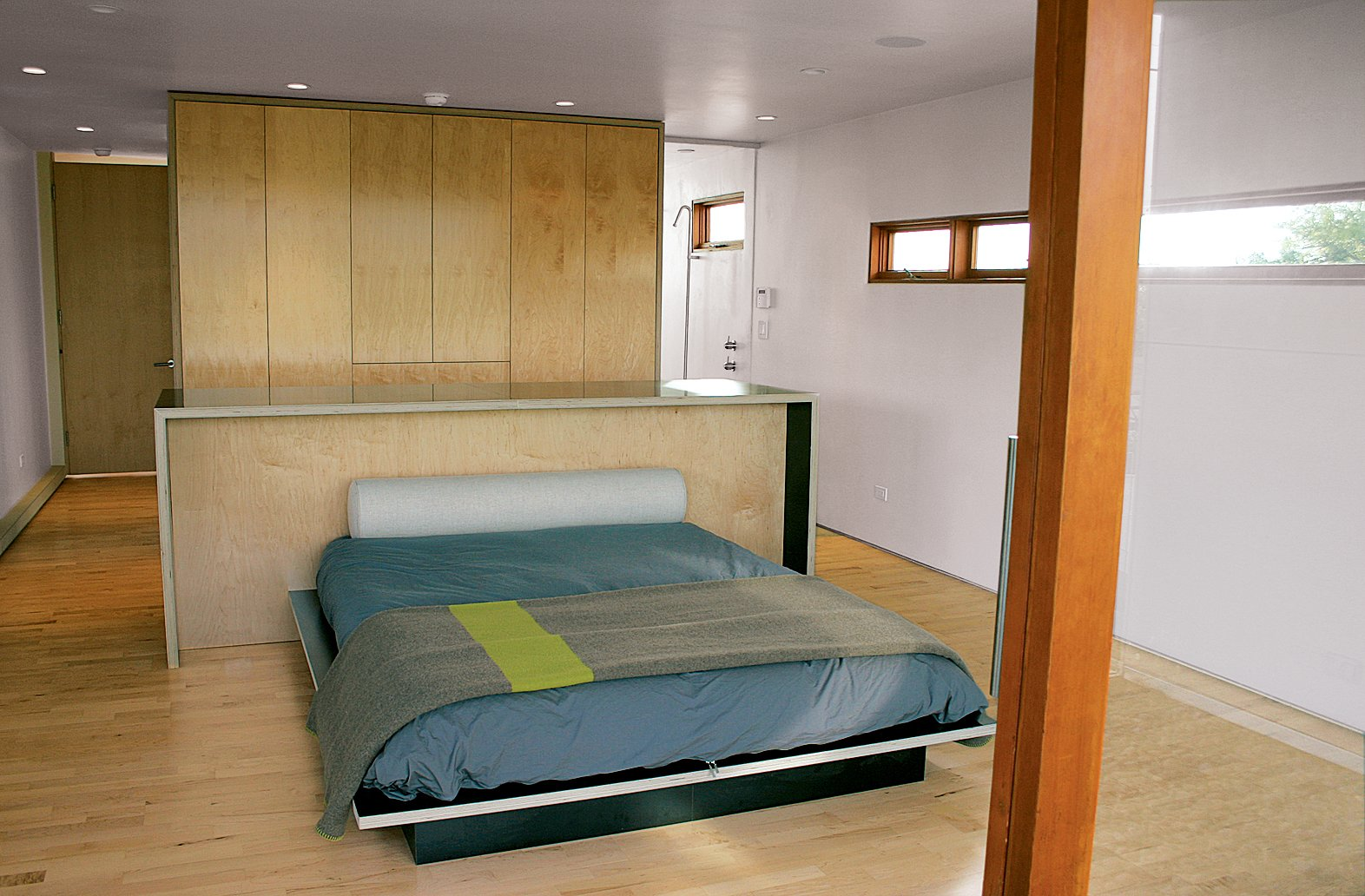 Bedroom, Bed, Recessed Lighting, Wardrobe, and Light Hardwood Floor The simplicity of the design is complemented by the unfussy use of materials, including the exposed edges of the bedroom furniture and paint-free drywall.  Photo 4 of 5 in Building Green in Santa Monica