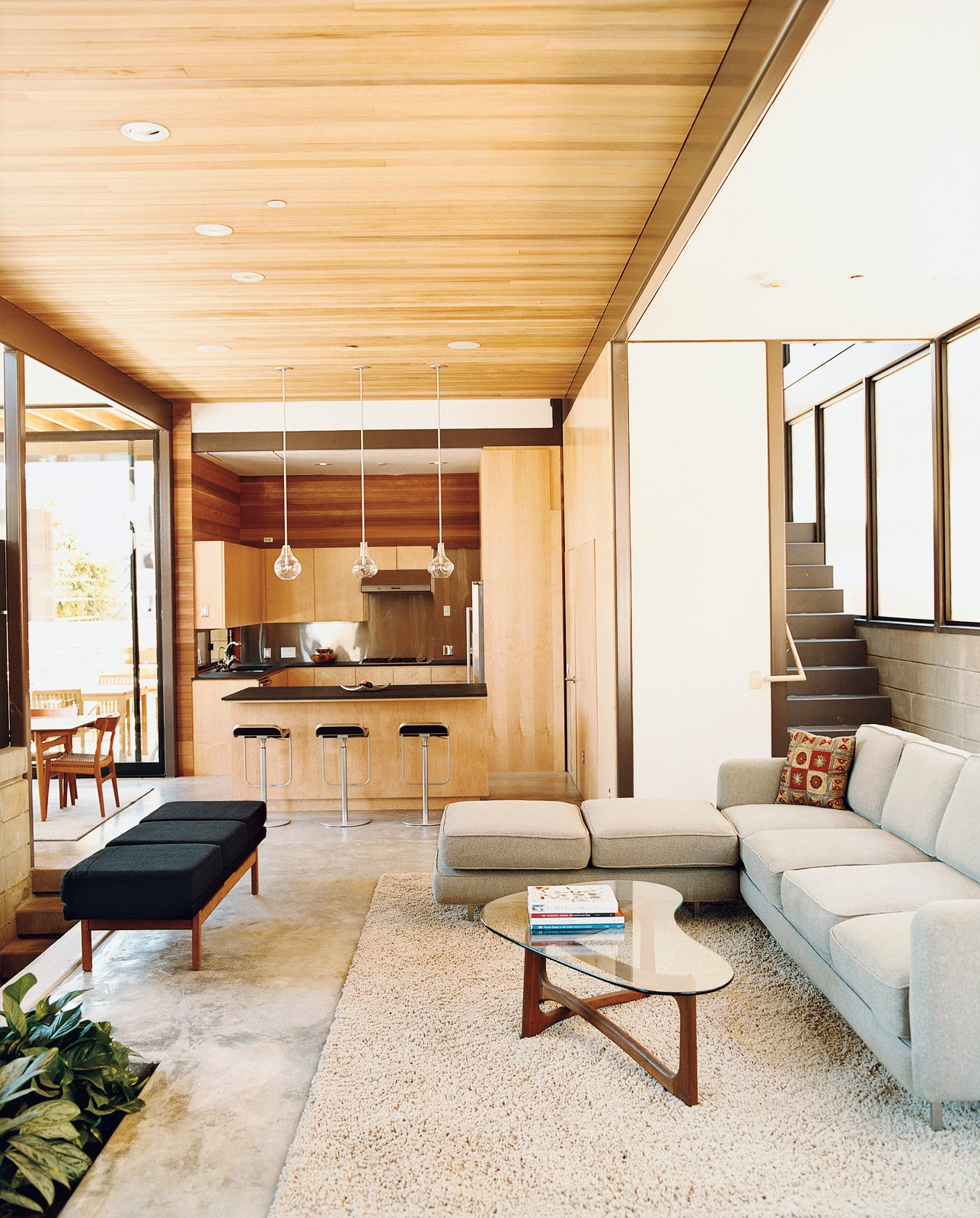 Living Room, Sectional, Coffee Tables, Pendant Lighting, and Bench A view of the lower living space on the ground floor. Green materials used include the FSC-certified cedar on the ceiling, Permlight LED downlights, and a floor of polished concrete with fly ash mix with radiant heating underneath. The couch was designed by Glenn's interior designer, Heidi Toll Design.  Photo 2 of 7 in LEEDing the Way