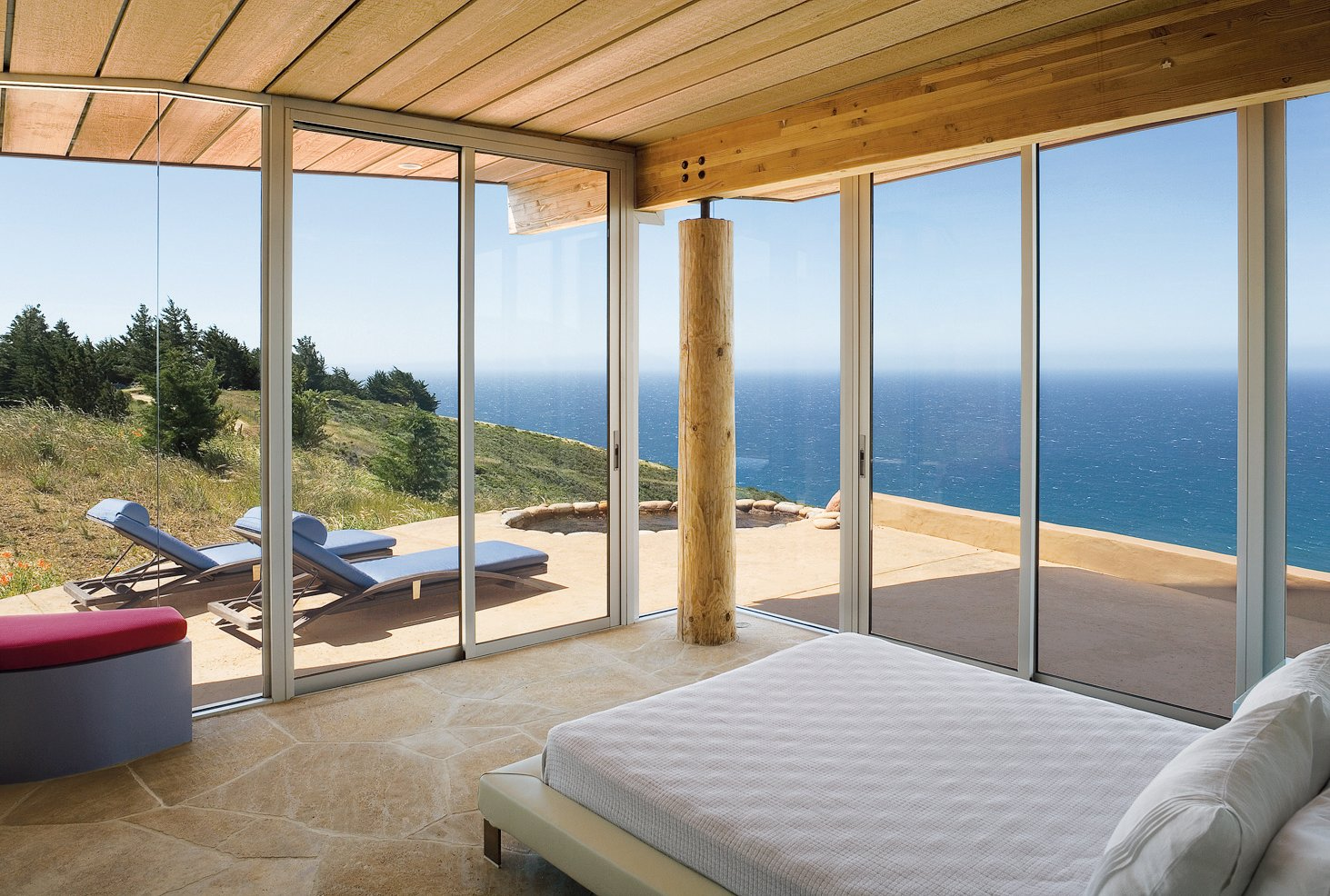 Bedroom, Bed, and Bench Two walls of floor-to-ceiling windows in the master bedroom frame expansive vistas of the Pacific Ocean.  Photo 4 of 6 in Big Sur: Going Coastal