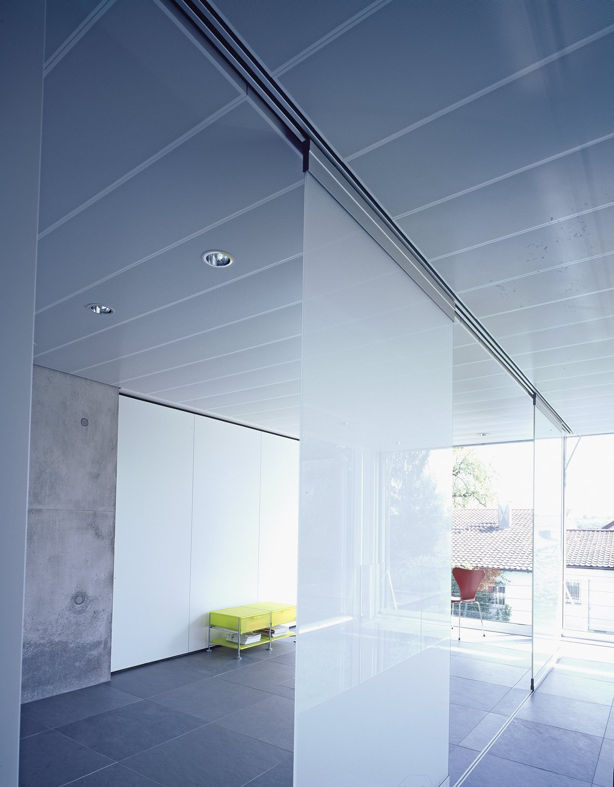 The movable glass partitions in the second floor of the office space provide privacy and translucent natural light (the space also serves as a guest room).  Photo 5 of 6 in A Tale of Two Houses
