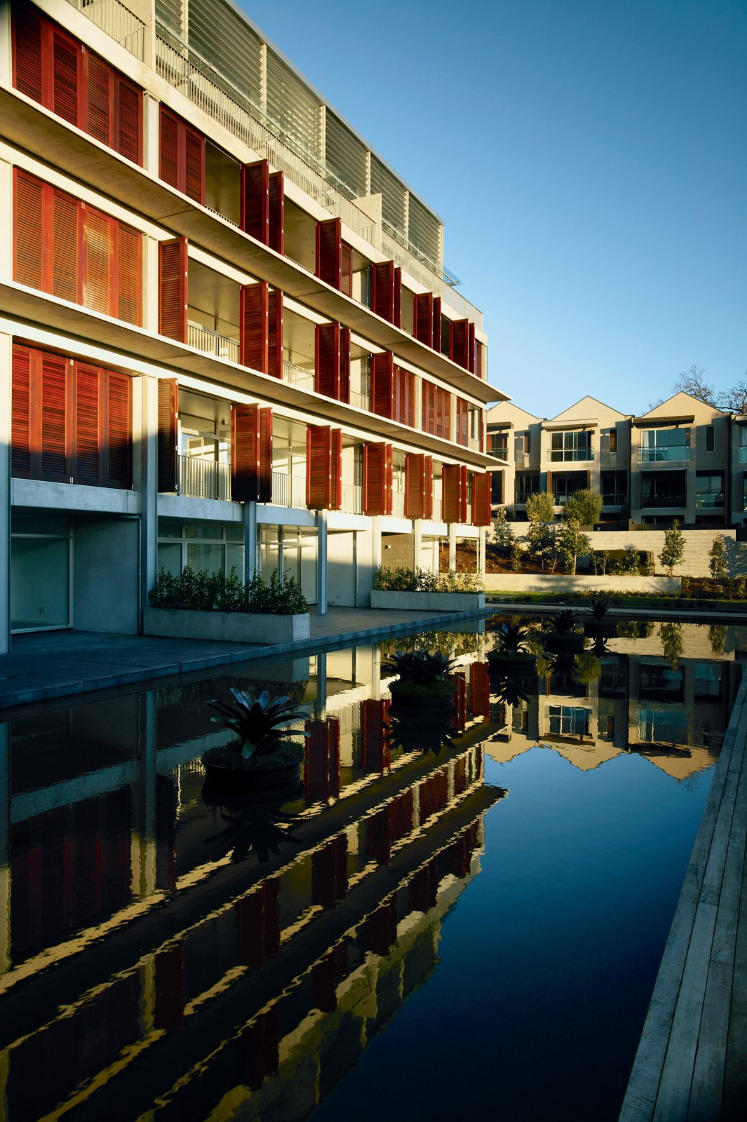 Garden-facing apartments benefit from an evaporative cooling effect off the pools; during hot afternoons, they're shielded by wooden shutters that can be completely closed.  Photo 7 of 8 in Density Down Under