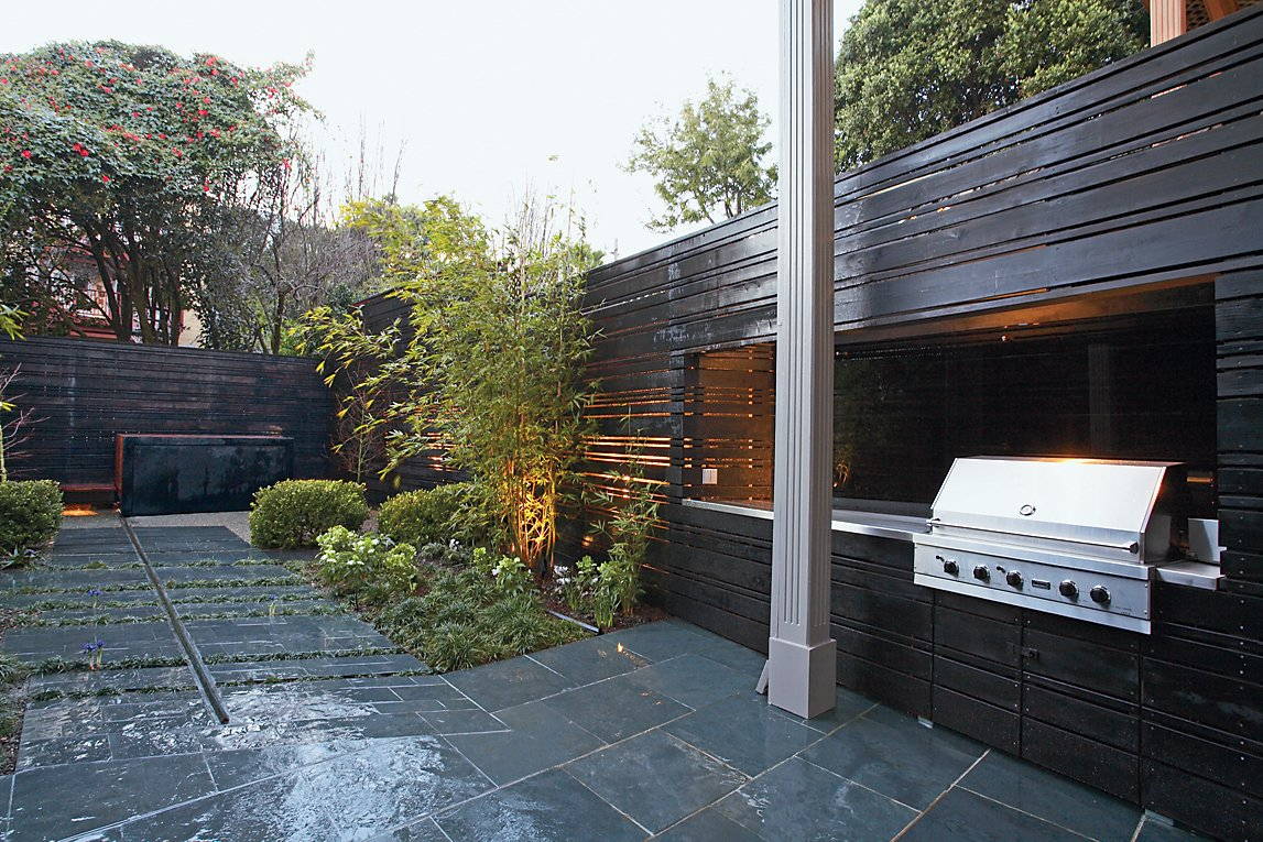 The landscape architects expanded an existing stone patio to include a bamboo grove, a boxwood hedge, and the ipe-and-steel hot tub.  Photo 3 of 4 in Stoked to Soak