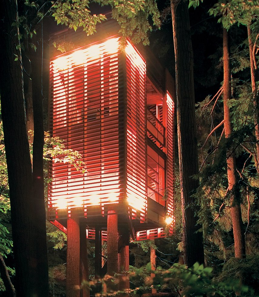 """Exterior, Wood Siding Material, Cabin Building Type, Treehouse Building Type, Tiny Home Building Type, and Flat RoofLine """"This was really a parameter-driven project,"""" explains Lukasz Kos, a Toronto-based designer and cofounder of the architecture firm Testroom. """"That is, I had to let the trees decide how the tree house would be.""""  What the trees decided, apparently, was that they wanted a gracefully slender, Blade Runner–like elevator lodged between them. They also decided they didn't want to be too mutilated in the process. Kos responded to their needs with the low-impact 4Treehouse, a lattice-frame structure that levitates above the forest floor of Lake Muskoka, Ontario, under the spell of some witchy architectural magic.  He created this effect by suspending the two-ton, 410-square-foot tree house 20 feet above the ground with steel airline cables. With only one puncture hole in each of the four trunks into which the cable is anchored, the trees get away almost entirely unscathed, and the structure attains the visual effect of being suspended weightlessly in midair.   At the base of the tree, a staircase rolls on casters upon two stone slabs, allowing occupants to enter and exit regardless of how much the tree house may be swaying or rocking in the wind. Solid plywood walls punctuated by a floor of red   PVC constitute the """"opaque"""" base story, which is largely protected from the outside elements. """"The idea was to have the tree house open up as it gained elevation,"""" explains Kos. The second story is surrounded by a vertical lattice frame, allowing for breezes, air, and light to filter softly through walls while still establishing a visual perimeter between outside and inside space. At top, the tree house is completely penned in, a suspended patio with a ceiling of sky.  br> br>Photo by Lukasz Kos.  Photo 91 of 101 in 101 Best Modern Cabins from Suspended Habitation"""