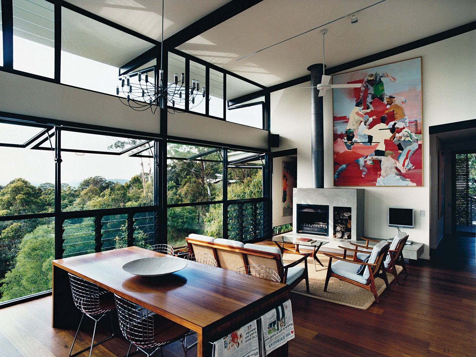 Living Room, Medium Hardwood Floor, Standard Layout Fireplace, Chair, Wood Burning Fireplace, Pendant Lighting, and Sofa The open-plan living room was inspired by the couple's previous residence, a London loft. The paintings are by Dunlop. The louvered floor-to-ceiling windows, ceiling fan, and sliding deck doors usher in sea breezes and encourage good air circulation.  Photo 4 of 12 in Hillside Family Home in Australia