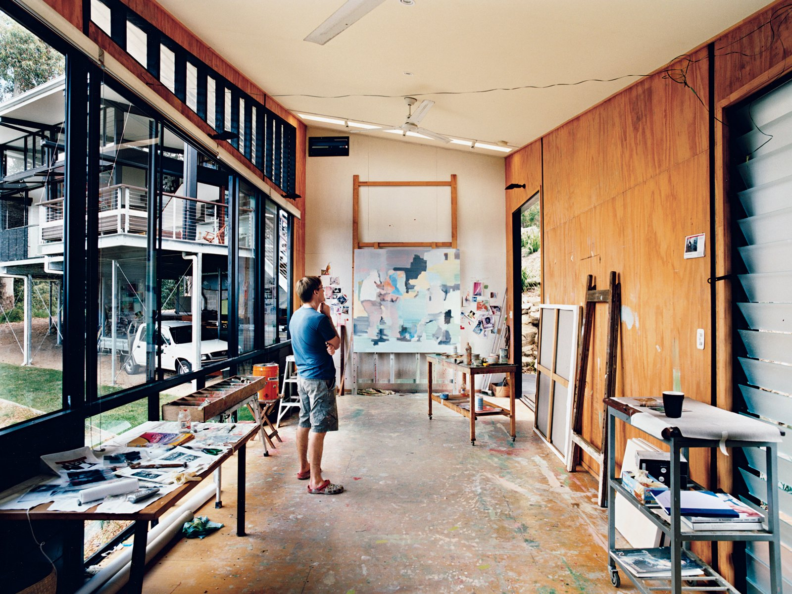 In his detached painting studio, Dunlop considers a work in progress. The building is oriented east-west to avoid direct sunlight, and the long, narrow shape enables the artist to get some distance from his paintings as he works. An oversize front door and angled ceiling accommodate extra-large canvases; the plywood walls and floor can   ably endure a beating, or, as is more likely, stray splashes of paint. Tagged: Office and Craft Room.  Photo 6 of 12 in Hillside Family Home in Australia