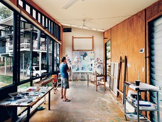 In his detached painting studio, Dunlop considers a work in progress. The building is oriented east-west to avoid direct sunlight, and the long, narrow shape enables the artist to get some distance from his paintings as he works. An oversize front door and angled ceiling accommodate extra-large canvases; the plywood walls and floor can <br><br>ably endure a beating, or, as is more likely, stray splashes of paint.