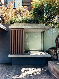 The glass and wood walls of the bathhouse, like other retractable panels on the house, <br><br>offer shade with a view.