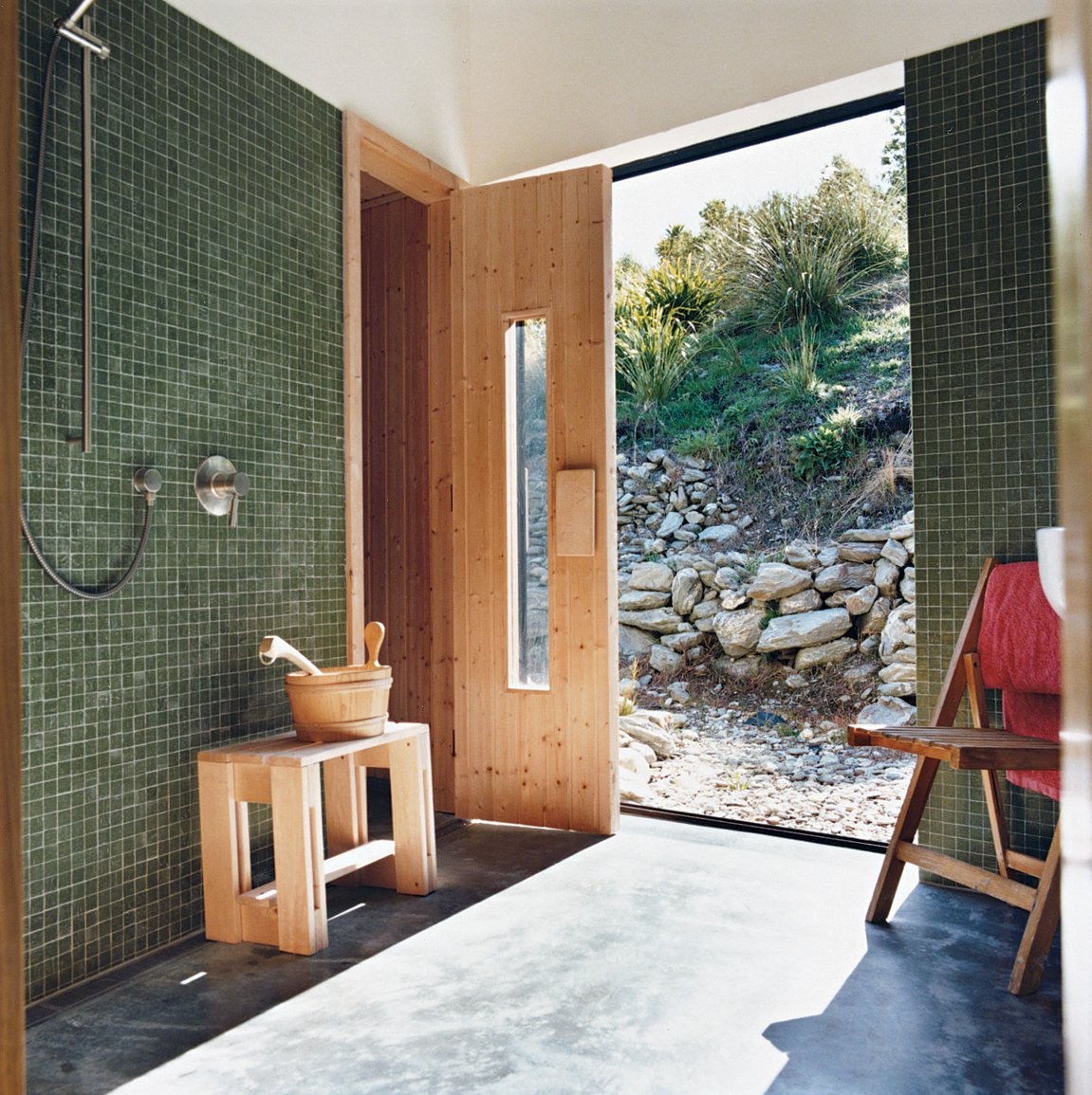 Bath Room, Concrete Floor, Glass Tile Wall, and Open Shower Queenstown gets cold in winter, hence the installation of a sauna. Outside, the landscaping was kept deliberately casual, with rock walls and gravel paths.  Photo 6 of 12 in Nature Nurtured