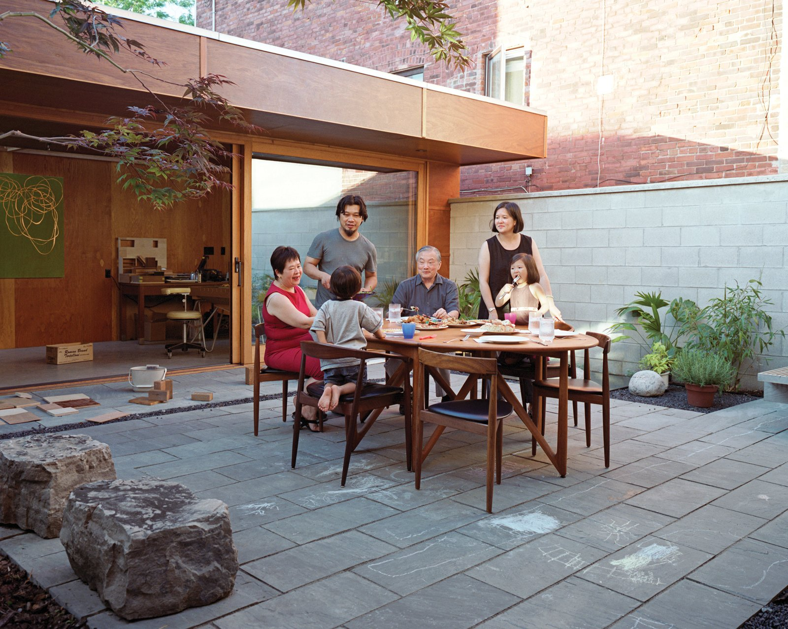 """The main courtyard is a """"communal"""" space, Tan says, and the couple keeps a second teak dining set at the ready for occasions when family or friends come for a meal.  Photo 15 of 17 in Inside Job"""