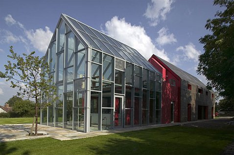 The house, built by de Rijke, Marsh and Morgan (dRMM), is a 3-in-1 building that slides along railroad tracks recessed into the concrete foundation. A greenhouse-like glass interior structure is exposed through the sliding movement of the red rubber and larch sheaths that form the exterior walls.  Photo 1 of 1 in Sliding House