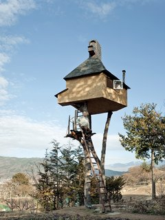 """Fujimori's retreat in Nagano, The Too-High Tea House, which is adorned with a roof of hand-rolled copper sheets, seems precariously perched atop a pair of tree trunks 20 feet in the sky. Why two? """"One leg is dangerous and three legs are too stable and boring."""""""