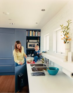 Julie enjoys her new kitchen with son Emerson. She wanted to conceal as many appliances as possible, so Deam disguised the Sub-Zero refrigerator and Miele dishwasher with panels from Downsview Kitchens that match the cabinets, giving the kitchen a clean, uncluttered appearance.
