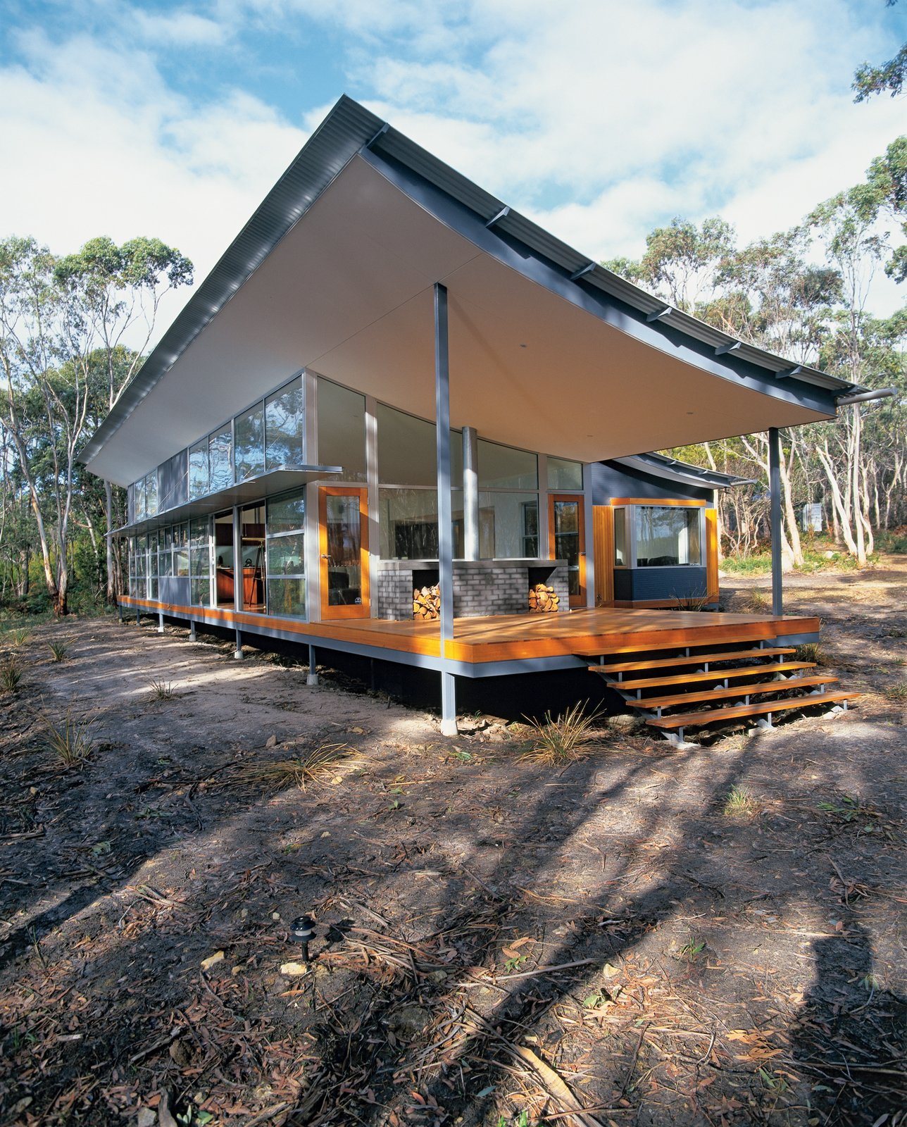 Exterior, House Building Type, and Shipping Container Building Type Solar panels mounted on a shipping container onsite (not pictured) heat this curvy house in Tasmania. The swooping roof cantilevered over the west-facing desk mitigates the intense afternoon sun.  Photo 2 of 4 in Tait Modern
