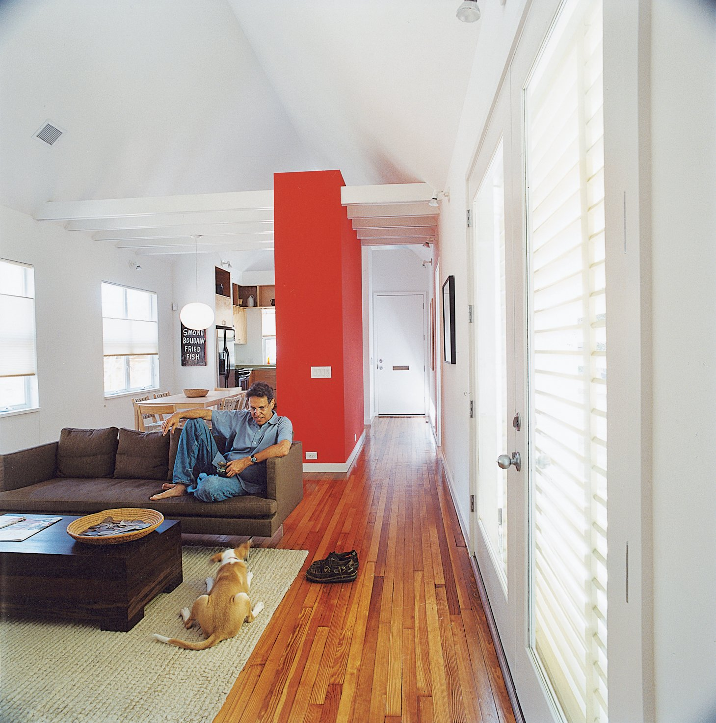 Living Room, Sofa, Medium Hardwood Floor, and Coffee Tables Kaplan and his dog Bella were able to splurge on a sofa from Ligne Roset after the house priced out at less that $100 per square foot.  Photo 9 of 45 in 45 Pets in Beautiful Modern Homes