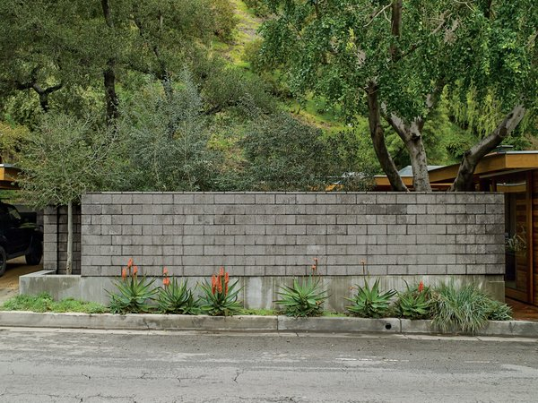 A wall of burnished concrete block protectively isolates their indoor and outdoor living areas from the busy road.  Photo 6 of 12 in Compound Addition