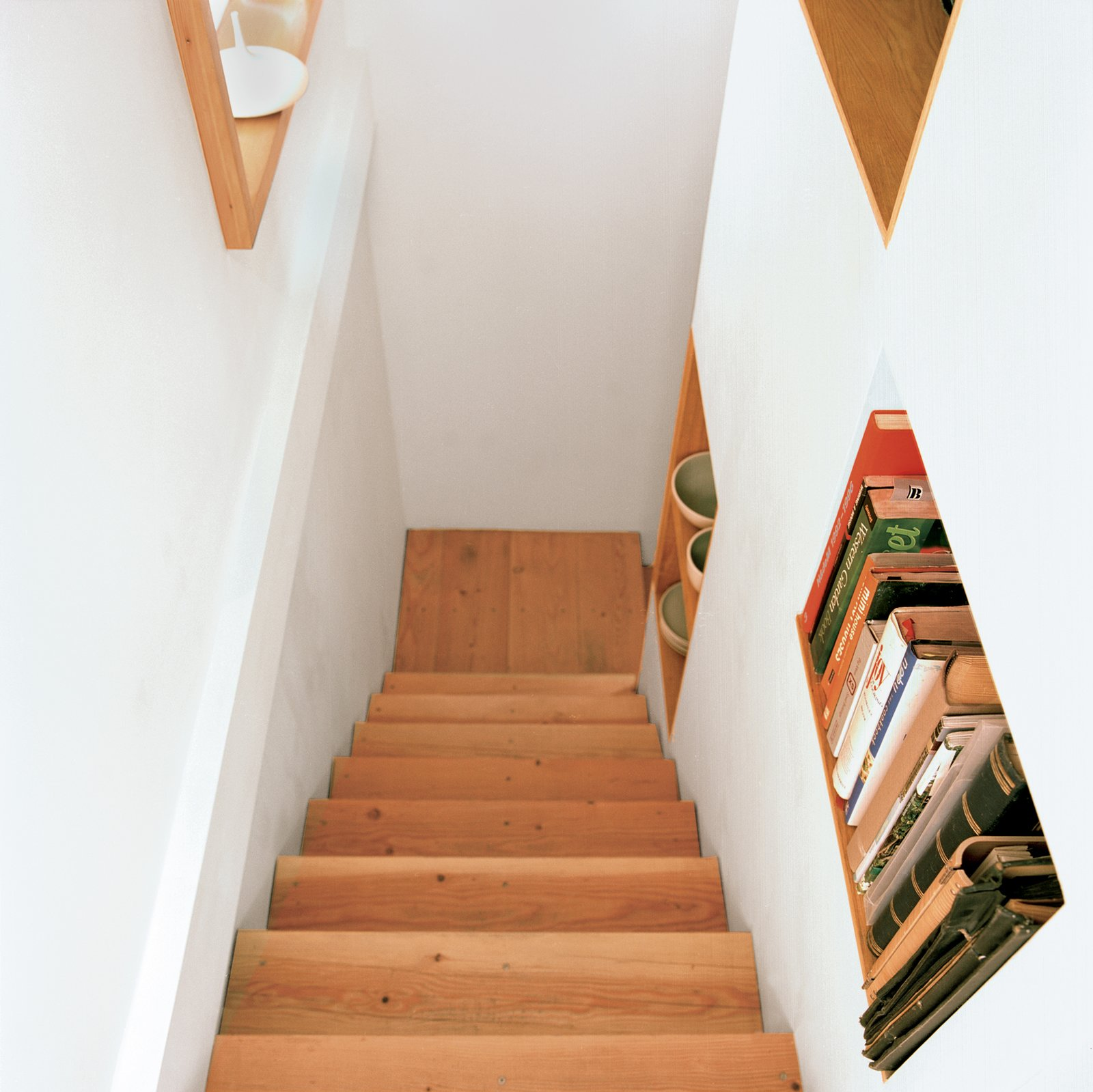 Staircase and Wood Tread The stairway features built-in shelving that's accessible from both sides.  Photo 9 of 9 in Built-In Style