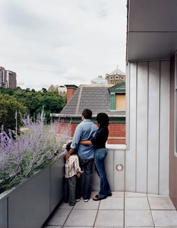 "Harlem Renaissance - Photo 10 of 11 - Yvette, Adrian, and their son Julian survey the view from the top-floor terrace. ""I've never been fond of modernism—I find it cold,"" Adrian admits. ""But having this house, I have <br><br>to say, it's growing on me."""