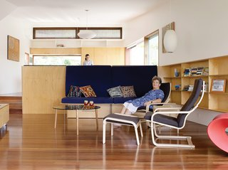 Hannah Ferguson relaxes in her living room. Her daughter Joanna prepares dinner in the open kitchen, behind and above the plywood banquette designed by the architects.
