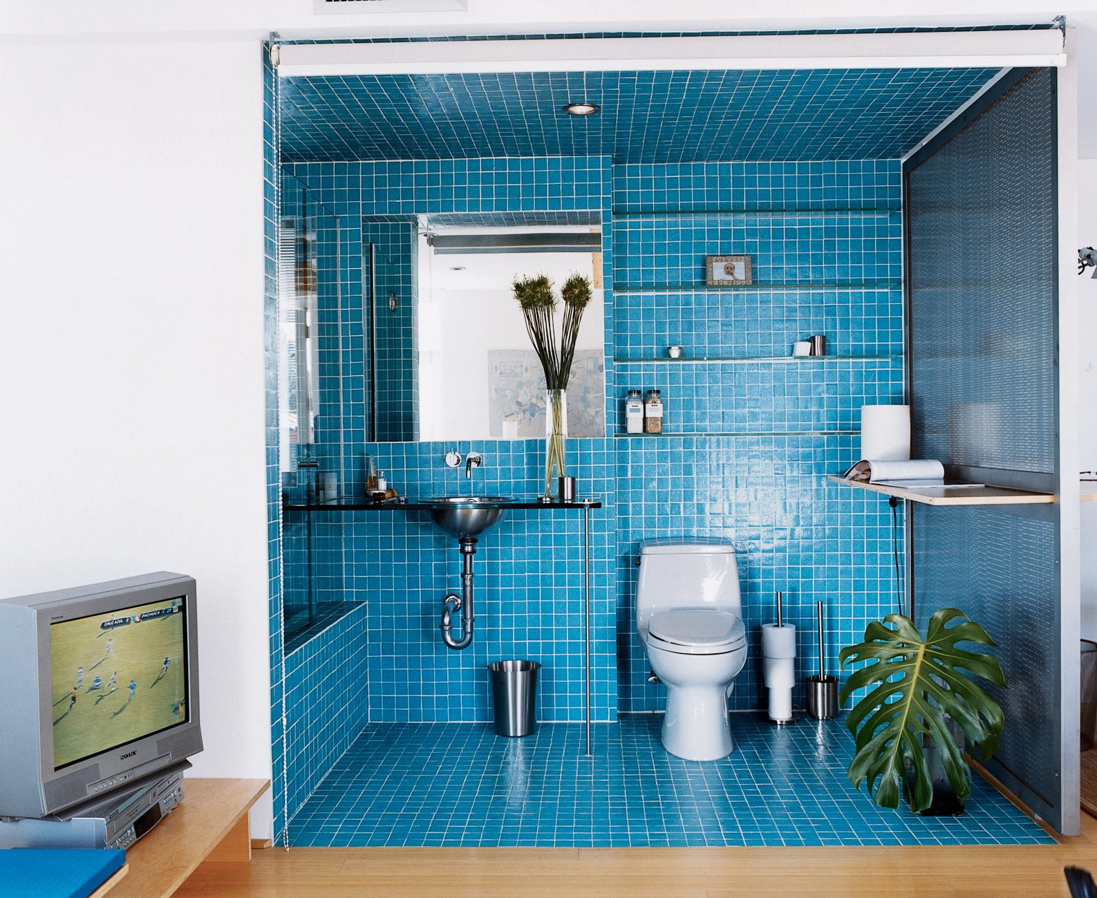 A roll-down shade encloses a guest bath on the lower level. The bath tile is two-by-two Daltile mosaic. The sink is from Kroin.  Photo 9 of 12 in Way Out West