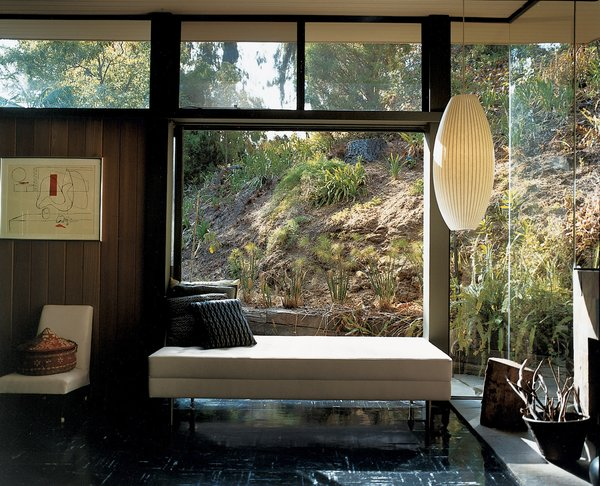 Near floor-to-ceiling window walls frame views of the landscaped hillside.
