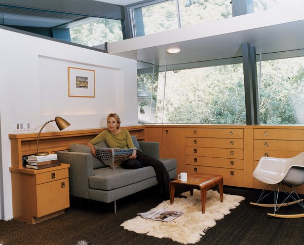 """Buckner takes time out for the newspaper and a cup of tea in a lounge off of the couple's bedroom. The bedroom, which sits within the cantilevered section of the house, was at one time a covered deck. The storage units are from a later renovation, but Buckner, who has expert knowledge of all of the original MHA homes, surmises that """"something very similar"""" would have been in its place."""