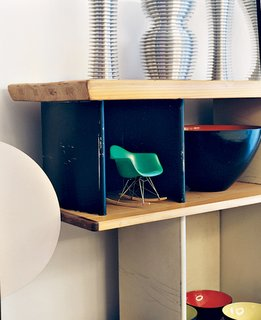 A miniature Eames rocker nestles in a Charlotte Perriand bookcase.