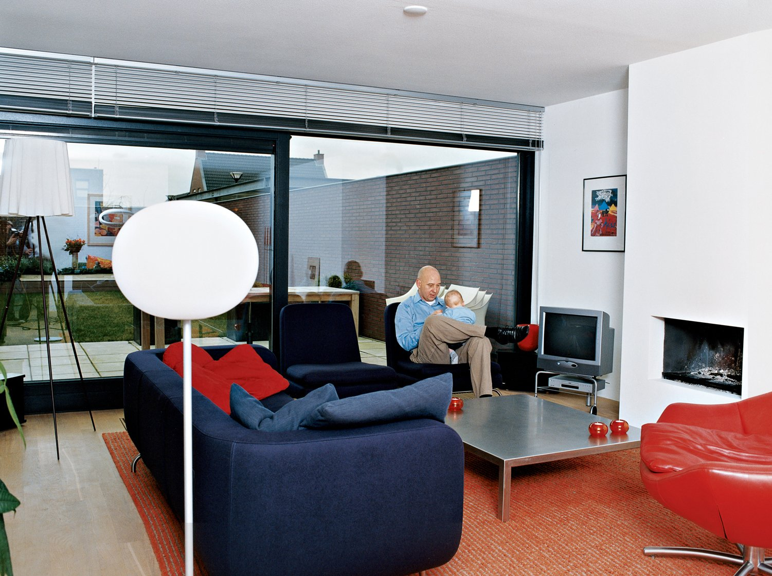 "Living Room, Sofa, Chair, Light Hardwood Floor, Standard Layout Fireplace, and Floor Lighting In the living room, Caspar educates his young son Roemer about the finer points of modern design. The red leather Gigi is van den Berg's racy yet refined swivel armchair. Looking at this chair, it comes as no surprise that the designer drives a Porsche. ""It's from the late '90s, but it's already a classic,"" says Caspar. ""I just love the versatility of this one—you can sit forwards or sideways in it."" Van den Berg also designed the stainless-steel coffee table. The purple sofa was designed by Rodolfo Dordoni, and the Glo-Ball lamp is by Jasper Morrison.  Photo 11 of 20 in 20 Modern Living Rooms from Furniture Fascination"
