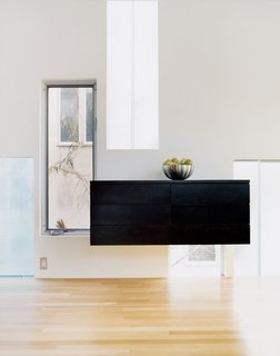 A custom-fabricated sideboard of birch, in a coffee-colored stain, finds its niche among the gathering of windows.