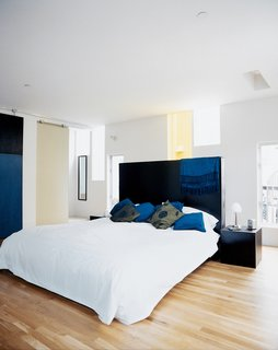 The narrow windows flood the master bedroom with light, while providing privacy. The dark-stained woods of the custom headboard and nightstands, all designed by the architect and built by Solicraft, cohesively tie the furnishings to elements like the bedroom sliding door and exterior concrete paneling.