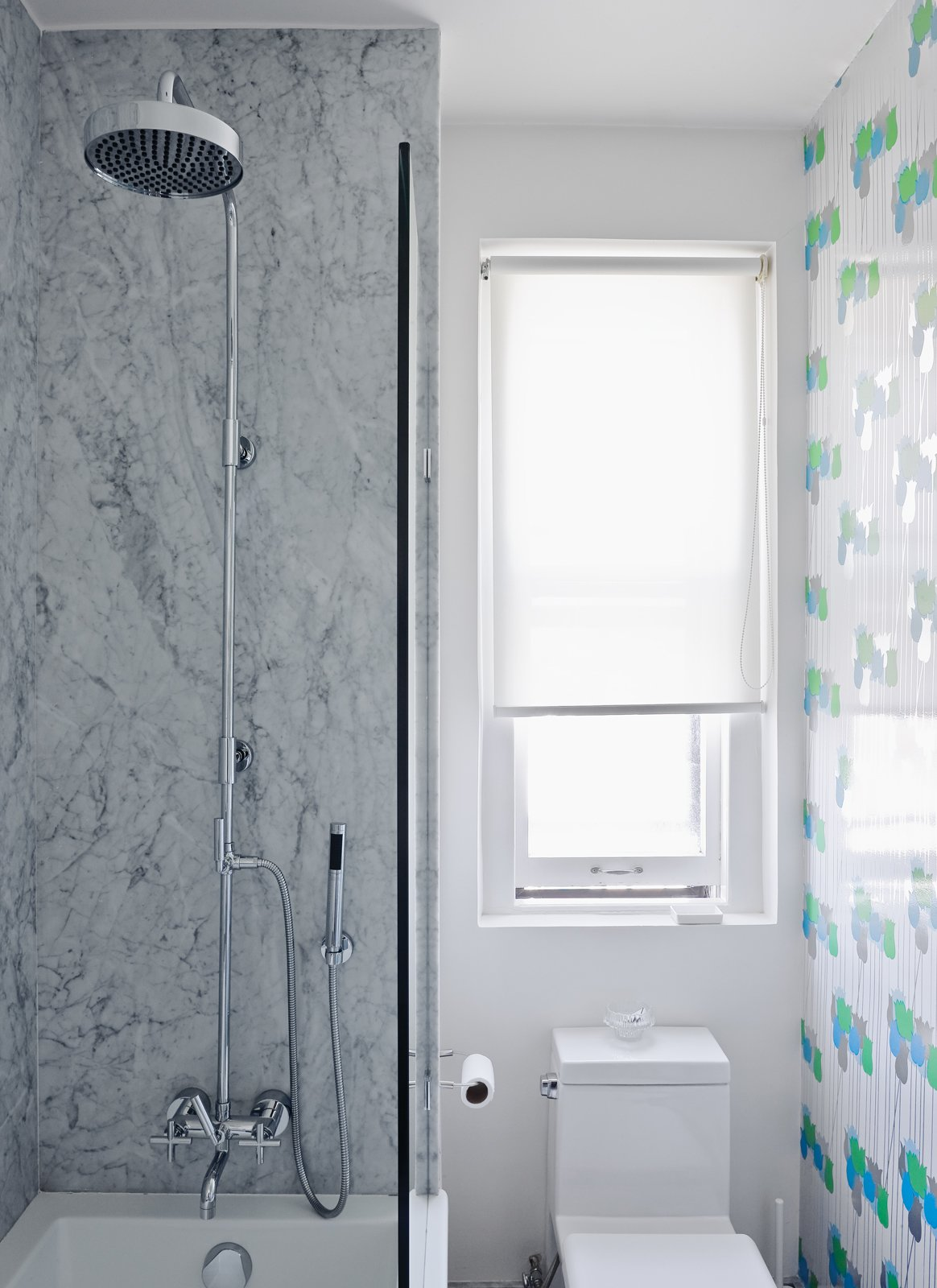"""Bath Room In the bathroom, the gray Carrara walls are offset by bright tulip-patterned wallpaper, circa 1970, from Secondhand Rose in Tribeca. The toilet is a Philippe Starck """"jet action"""" model from Duravit.  Photo 11 of 13 in Creative Renovation in Brooklyn"""
