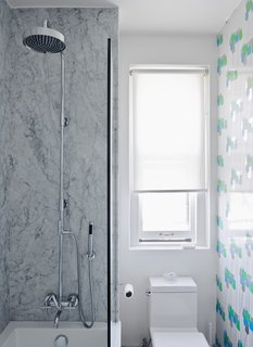 "Brooklyn–based graphic designers Jeanette and Mike Abbink worked with Architecture + Construction to renovate their residence. In the bathroom, the gray Carrara walls are offset by bright tulip-patterned wallpaper, circa 1970, from Secondhand Rose in Tribeca. The toilet is a Philippe Starck ""jet action"" model from Duravit. Read the entire article here."