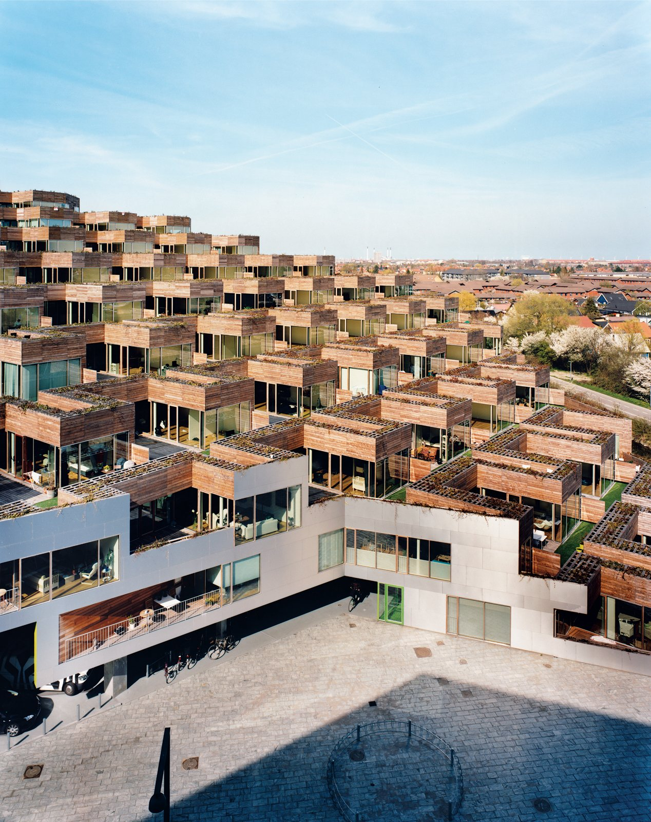 """Every apartment has a terrace measuring around 1,000 square feet, with both private and semipublic spaces. """"The cool thing about a garden is it's yours,"""" says architect Bjarke Ingels. """"If you're on the wooden part, you can suntan in your bikini bottom or go without pants."""" If, however, you walk out onto the artificial turf, you can see what's going on with your neighbors (and they can see you).  Photo 4 of 20 in Mountain Dwellings Urban Development in Copenhagen"""