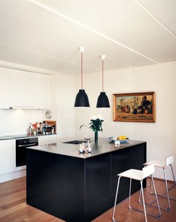 White walls, oak floors, and wooden window panes exude a calm, Danish-modern vibe. A stainless steel kitchen island, designed by BIG, is lit by Cecilie Manz's Caravaggio lights.