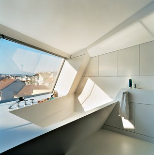 The Penthouse Has Landed - Photo 5 of 16 - The cavity for the bathtub is part of the same continuous form-world as House Ray 1's sloping roofscape. The white tub is made from Corian; the faucet is by Dornbracht.