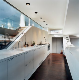 The Penthouse Has Landed - Photo 9 of 16 - The kitchen window looks out to stairs that lead up to a small roof terrace. The kitchen faucet is byDornbracht. The recessed lighting is by Guzzini.