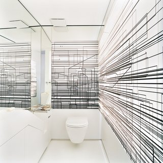 The Penthouse Has Landed - Photo 12 of 16 - The walls of the toilet room are decorated with an abstract composition of overlapping black lines printed on a screen that is lit from behind.