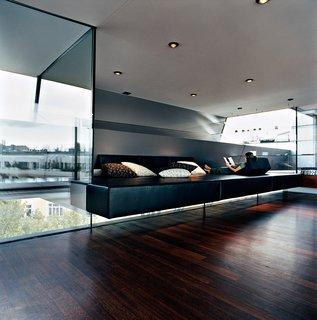 "The Penthouse Has Landed - Photo 16 of 16 - Meissl and Delugan's favorite part of the house is definitely the ""relaxation zone,"" which features a black leather platform of their own design that appears to float between layers of tempered glass. The pillows are by Herman Miller."