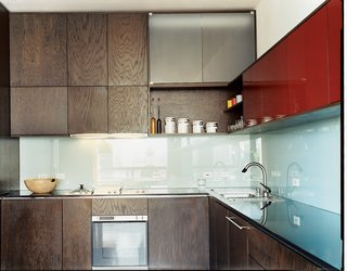 MS-31 designed and built all the kitchen cabinetry, as well as the dining table, in collaboration with Archkinetics. The frosted-glass backsplash offers easy cleaning.