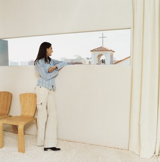 Maricarmen takes in the view from her and Sebastian's bedroom window, which frames the church's cross. White curtains and a flokati rug add a welcome layer of calmness in a house that's also home to their office and two young children.