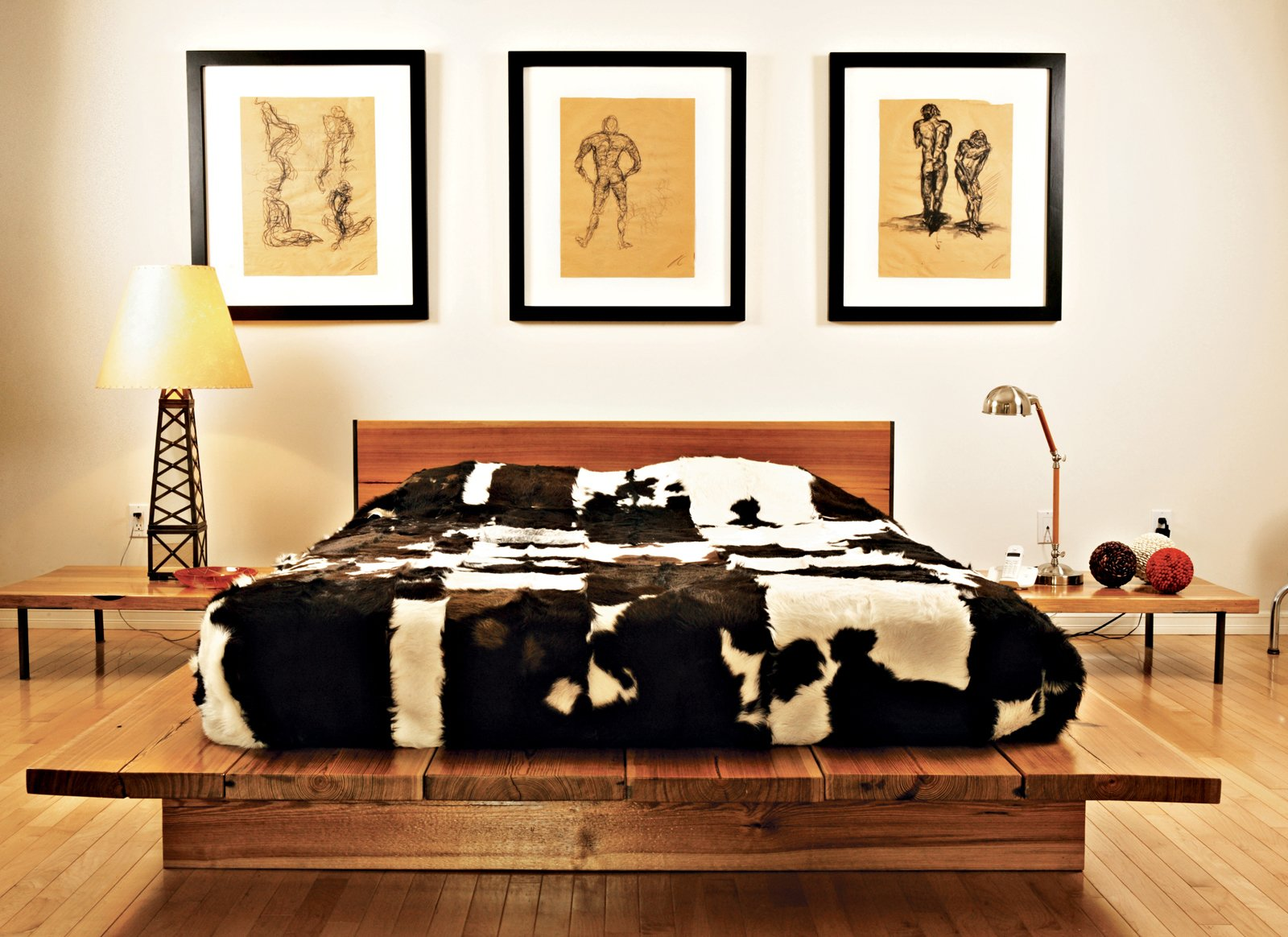 Bedroom, Bed, Table Lighting, and Medium Hardwood Floor Graphic cowhides on the guest bed, the dining chairs, and the living room floor unite the varying levels of the house. That design element—and the cute oil derrick lamp in the guest bedroom—remind you that, yes, you are in Texas. The drawings are by Erik's brother Jair, an architect working in New York.  Photo 3 of 8 in Home Cooking