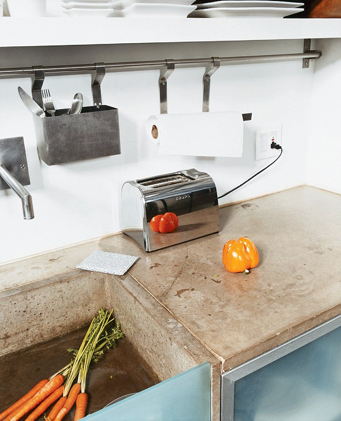 Kitchen and Concrete Counter The cast-concrete sink, glass detailing, and steel appliances add to the clean, minimal, space-saving feel of the kitchen.  Photo 5 of 9 in Cutting Up a Mini Loft in Los Angeles