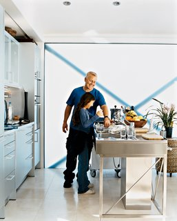Picard and his daughter, Alexis, who visits on weekends, enjoy cooking fresh ingredients like fish or artichokes in the Miele steam oven. The translucent glass wall provides plenty of natural light and gives the aluminum-and-stainless-steel kitchen a soft white glow.