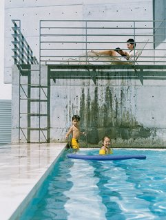 The kids and their mother relax in the pool area, their figures framed against a monochromatic background of steel and concrete.