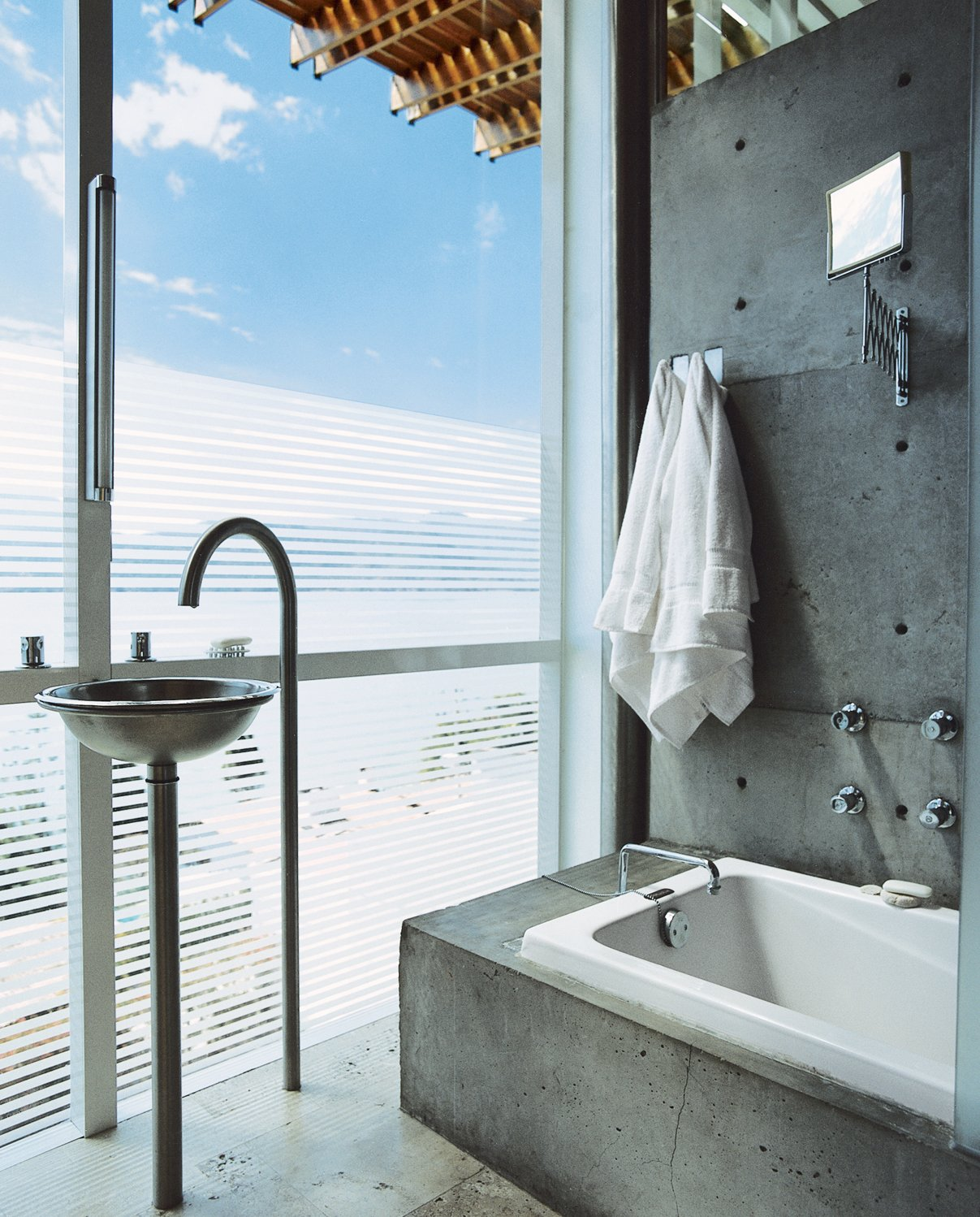 Bath Room, Concrete Floor, Drop In Tub, Concrete Wall, and Pedestal Sink In the master bath, the architect managed to combine privacy and a view by adding a horizontal-line pattern to the glass wall.  Photo 18 of 22 in Bath & Spa Intrigue from Reflections on a Lake