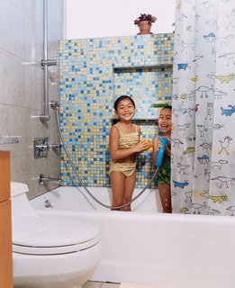 The sisters in their colorful bathroom with Kohler fixtures.