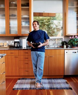 The architect at home in his kitchen with cabinetry that he also designed.